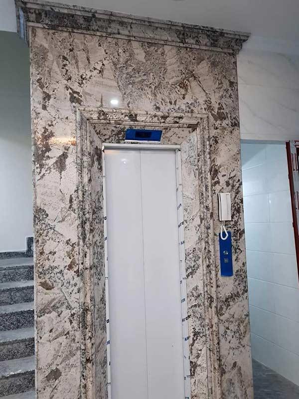 Mặt tiền thang máy đẹp đá trắng alaska